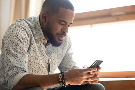 African American man using cellphone texting or browsing web