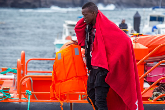 A migrant carries a life jacket after arriving aboard a Spanish maritime rescue boat, after being rescued at sea north of Spain's Canary Islands, on the island of Gran Canaria
