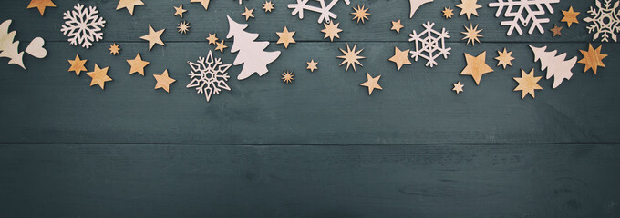 The beautiful christmas background with a lot of small wooden decorations on the white wooden desk.