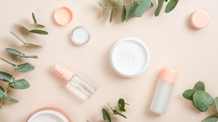 Flat lay composition with natural organic cosmetic products on beige background. Top view hand cream in jar, essential oil, skin lotion and eucalyptus leaves. Natural organic beauty product concept Fotobehang