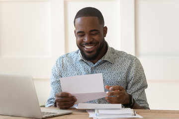 Happy biracial man feel excited get good news in letter