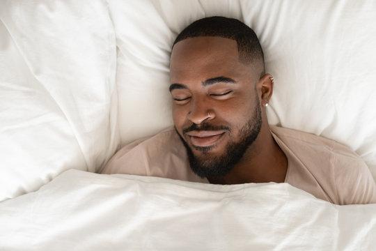 Calm biracial man sleeping seeing pleasant dreams