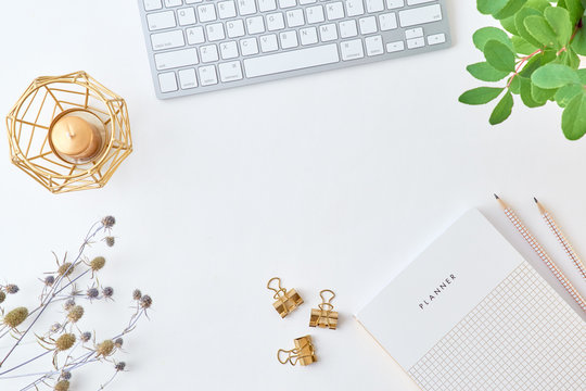 Blogger or freelancer workspace with keyboard, planner and branches with green leaves on light background