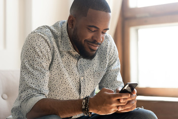 Smiling african American man feel happy texting on smartphone Fototapete