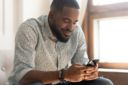 Smiling african American man feel happy texting on smartphone