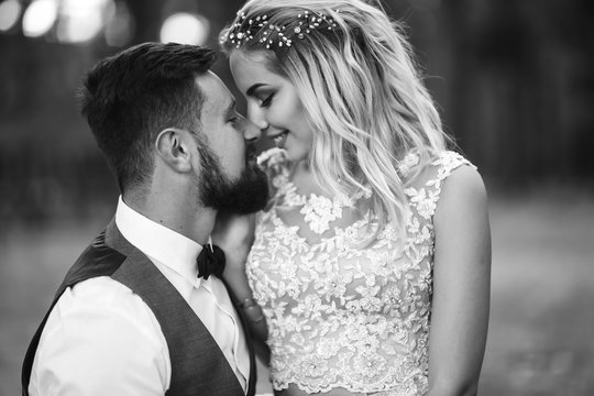 Sensual Black and white foto of bride and groom. Stylish couple of happy newlyweds posing and kisses in the park on their wedding day. Together. The concept of youth, love, fashion and lifestyle.