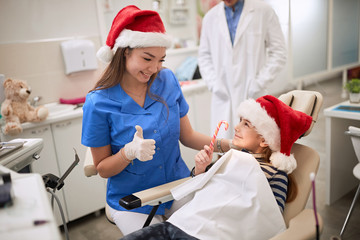Dentist woman in Santa hat examining tooth patient in ambulant.