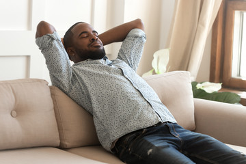 Calm african American relaxing on comfortable sofa at home Wall mural