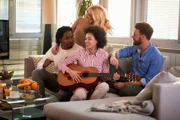 Friends enjoys at home with guitar