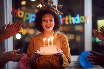woman blowing out her birthday candles and celebrating Birthday