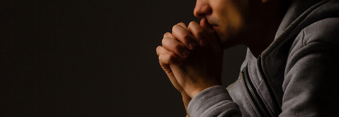 Religious young man praying to God on dark background, black and white effect