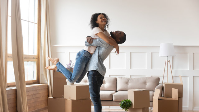 African husband lifting up wife happy family celebrating relocation day