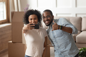 Happy african couple takes selfie photo carton boxes on background