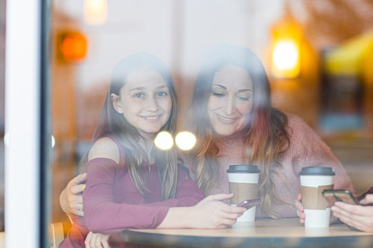 Mother and daughter sitting in cafe drinking coffee. One girl looking on the camera. woman looking on mobile phone. Picture through window.