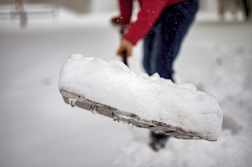 Closeup shot of snow on a snow shovel with a blurred background