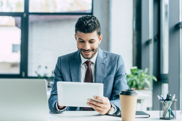 cheerful businessman using digital tablet while sitting at workplace