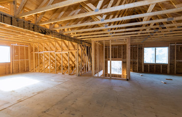 Beam built home under construction with wooden truss, post and beam framework frame house