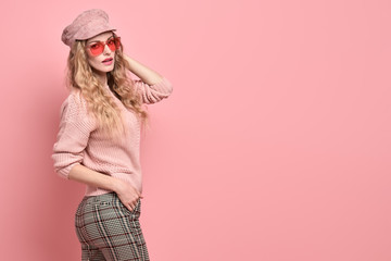 Fashionable woman in Trendy pink outfit, stylish hairstyle, makeup smiling. Young blonde in jumper, cap. Sensual beautiful model girl in stylish sunglasses, pastel fashion beauty concept on pink Wall mural