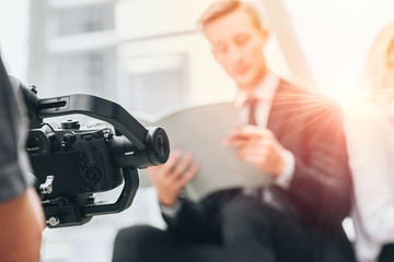 Videographer professional shooting record video usign gimbal camera stabilizer for anti shake device technology in businessman scene. Wall mural