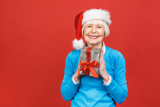 Happy mature woman with a gift. Isolated over red background. Beautiful stylish senior lady opening her Christmas gift. Elegant mature woman holding a red gift box.