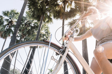 girl on bicycle on a summer day, in a tropical site with palm trees and sun rays in the background. Vintage style stock photo