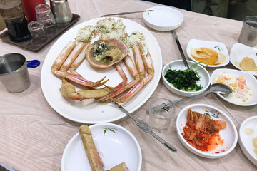 served crab on plate and various korean banchan