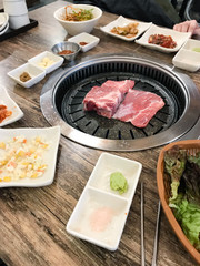 pieces of pork are frying in korean BBQ grill