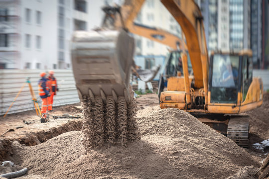 Yellow heavy excavator excavating sand and working during road works, unloading sand during construction of the new road