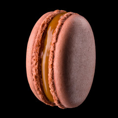 Papiers peints Macarons Macro photo of french caramel macaroon or macaron isolated on black background