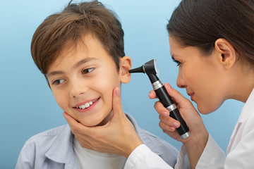 Fototapeta Little boy while ear exam. ENT doctor exam ear with otoscope on blue background