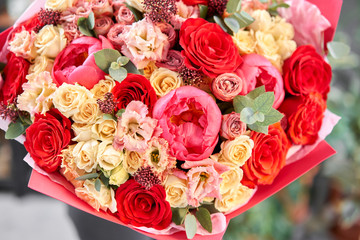 Red tones Beautiful bouquet of mixed flowers in womans hands. the work of the florist at a flower shop. Handsome fresh bouquet. Flowers delivery