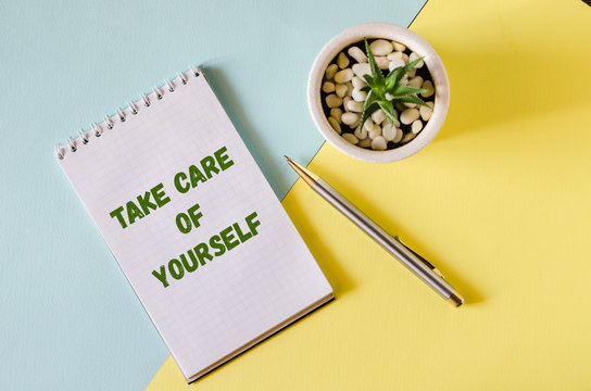 Take care of yourself. notebook and pen on a yellow-blue background.