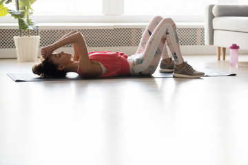 Exhausted young woman relax after workout at home