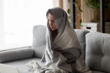 Ill girl wrapped in blanket suffering from cold
