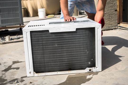a professional electrician is cleaning the window air conditioner on the roof top of a house with a wet napkin