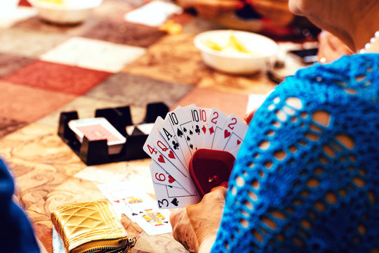 Close up of senior woman playing cards at table