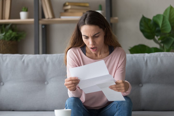 Shocked young woman stunned by bad news in letter