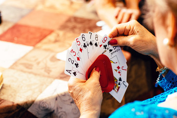 Senior woman's hands playing cards at table