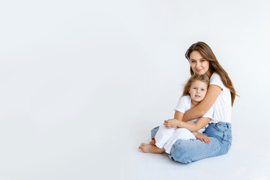Happy mom and daughter cuddling on a white background. Happy family concept