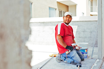 Bricklayer with tools kneeling on worksite