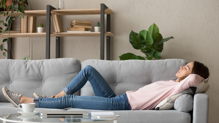 Stores photo Detente Tired young woman relax at home sleeping on cozy couch