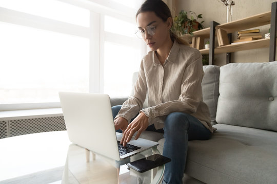 Focused young woman busy working on laptop from home
