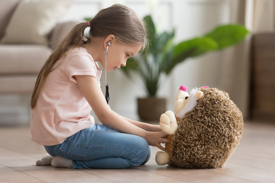Cute little girl play doctor game with toy hedgehog
