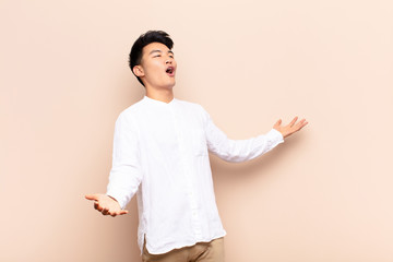 young chinese man performing opera or singing at a concert or show, feeling romantic, artistic and passionate against flat color wall