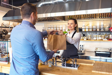 Happy waitress wearing apron serving takeaway food to customer at counter in small family restaurant.