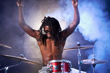 black young guy with dreadlocks wearing eyeglasses sit beating on drums with sticks, with naked...