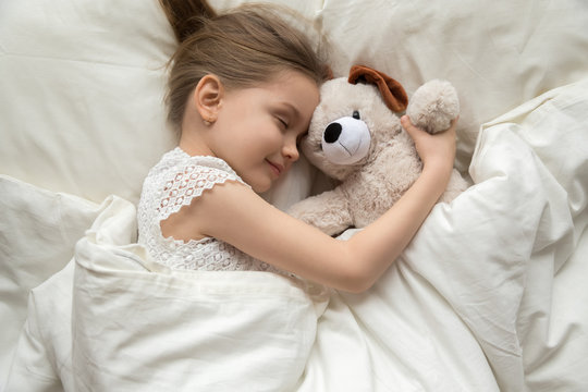 Preschooler girl hug teddy sleeping peacefully in cozy bed