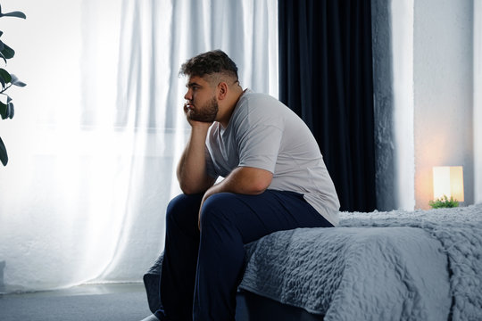 Depressed overweight man on bed at home