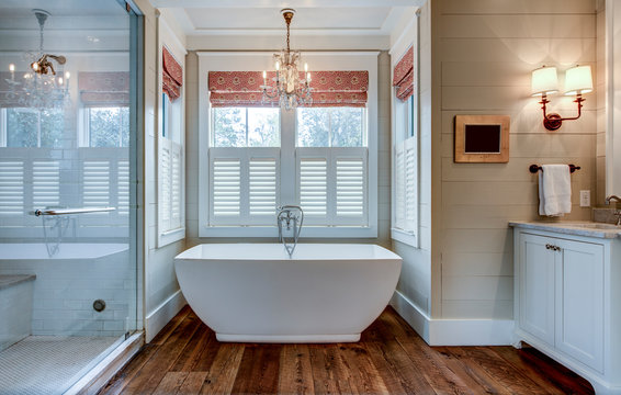 High end bathroom with large white bathtub and shiplap siding.