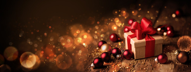 Abstract Christmas Banner  -  Gift box with red bow and baubles on wood  -  Magic dark golden bokeh lights background Fototapete